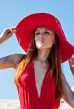 红色礼服的美丽的妇女在海滩 免版税库存图片