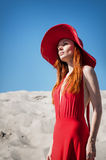 红色礼服的美丽的妇女在海滩 库存图片