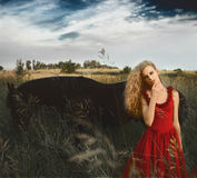 红色礼服的美丽的妇女在黑马前面 库存图片