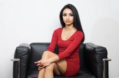 红色礼服的美丽的妇女坐黑椅子 免版税库存照片