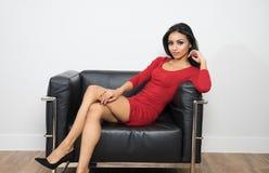 红色礼服的美丽的妇女坐黑椅子 库存照片