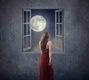 红色礼服的美丽的妇女走到与月亮的被打开的窗口的 图库摄影