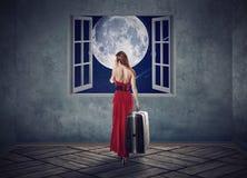 红色礼服的美丽的妇女走到与月亮的被打开的窗口的 免版税图库摄影
