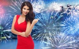 红色礼服的美丽的性感的妇女在烟花 免版税库存照片
