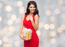 红色礼服的美丽的性感的妇女有礼物盒的 库存图片
