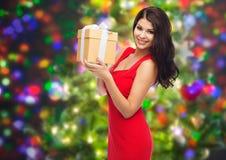 红色礼服的美丽的性感的妇女有礼物盒的 免版税库存照片