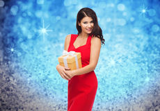 红色礼服的美丽的性感的妇女有礼物盒的 免版税图库摄影