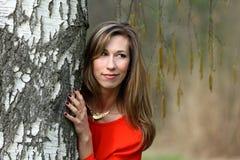 红色礼服的美丽的白肤金发的妇女 免版税图库摄影
