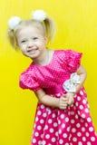 红色礼服的美丽的矮小的白肤金发的女孩有与一朵花的圆点的在黄色背景 图库摄影