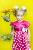 红色礼服的美丽的矮小的白肤金发的女孩有与一朵花的圆点的在黄色背景 免版税图库摄影
