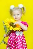 红色礼服的美丽的矮小的白肤金发的女孩有与一朵花的圆点的在黄色背景 库存照片