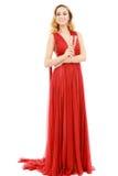 红色礼服的美丽的端庄的妇女有一杯的香槟c 库存图片