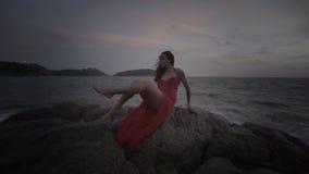 红色礼服的美丽的诱人的妇女开心的在岩石由海 免版税图库摄影