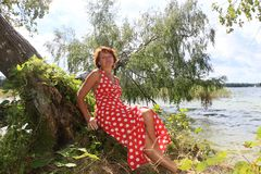 红色礼服的美女在湖附近 图库摄影