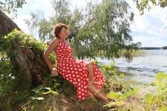 红色礼服的美女在湖附近 库存图片
