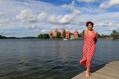 红色礼服的美女在湖附近 免版税库存图片
