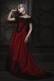 红色礼服的美妙的妇女 免版税库存图片