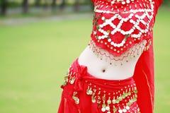 红色礼服的腹部接近的肚皮舞表演者 免版税库存图片