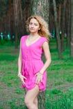 红色礼服的苗条女孩在树附近 免版税库存图片