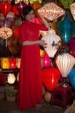 红色礼服的越南女孩卖纪念品中国人灯笼 免版税图库摄影