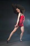 红色礼服的跳舞妇女在黑背景 库存图片