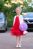 红色礼服的逗人喜爱的小女孩有气球的 图库摄影