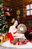 红色礼服的雪未婚与涉及圣诞树背景 免版税库存照片