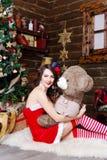 红色礼服的雪未婚与涉及圣诞树背景 库存图片