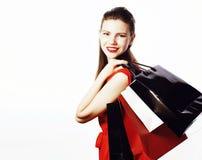 红色礼服的年轻俏丽的微笑的妇女有在白色背景在购物的袋子的隔绝的,生活方式真正的人民 免版税图库摄影