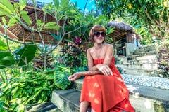 红色礼服的年轻时髦的女人在一个热带庭院里 放松在巴厘岛,印度尼西亚的愉快的妇女画象 免版税库存照片