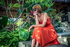 红色礼服的年轻时髦的女人在一个热带庭院里 放松在巴厘岛,印度尼西亚的愉快的妇女画象 库存照片