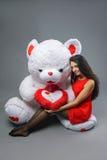 红色礼服的年轻美丽的女孩有大玩具熊软的玩具愉快微笑和使用的在灰色背景 库存图片