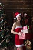 红色礼服立场的年轻性感的雪未婚在与圣诞节礼物的新年树 免版税库存图片