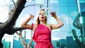 红色礼服舞蹈的华美的白肤金发的妇女在近的树和镜子表面之外 股票录像