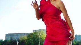 红色礼服跳舞的华美的白肤金发的妇女在街道上外面在慢动作 影视素材