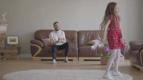 红色礼服跳舞的小滑稽的女孩在蓬松地毯的前景 有胡子的父亲坐 影视素材