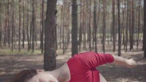 红色礼服跳舞的逗人喜爱的年轻女人在杉木之间的森林美丽的舞蹈家跳舞当代 ??  股票录像