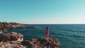 红色礼服身分的美女在岩石峭壁 在多岩石的海滩的少女身分用单独的手 短的礼服神色的女孩 股票录像