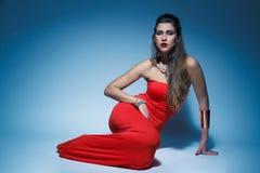 红色礼服长的头发的年轻魅力妇女 免版税库存图片