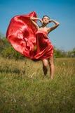 红色礼服飞行的新美丽的妇女在风 库存图片