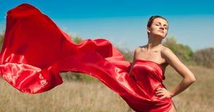 红色礼服飞行的新美丽的妇女在风 免版税库存照片