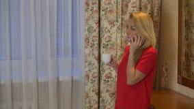 红色礼服饮用的咖啡的白肤金发的妇女和叫由手机 股票录像