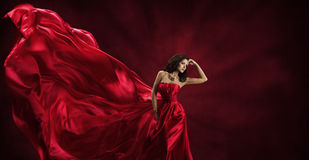 红色礼服,飞行时尚丝织物的妇女给模型穿衣