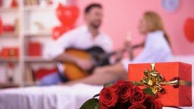 红色礼物盒和束玫瑰特写镜头,男性使用的吉他浪漫曲调 股票录像