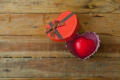 红色礼物盒和红色丝带和微型心脏里面在木backgr 免版税图库摄影