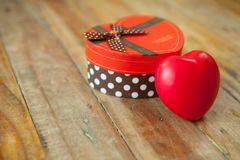 红色礼物盒和红色丝带和微型心脏里面在木backgr 免版税库存图片