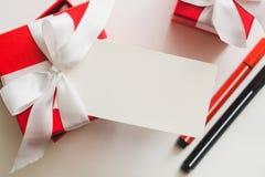 红色礼物盒栓与一条白色丝带、标志和卡片与拷贝空间在轻的背景 图库摄影