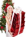 给红色礼物盒的圣诞老人帽子的圣诞节女孩。 免版税库存照片