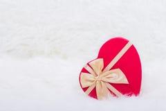 红色礼物盒以心脏的形式与米黄弓的在白色毛茸的后面 库存照片