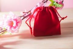 红色礼物袋子和李子在老破旧的木表概念圣诞节和Newyear开花 免版税库存图片